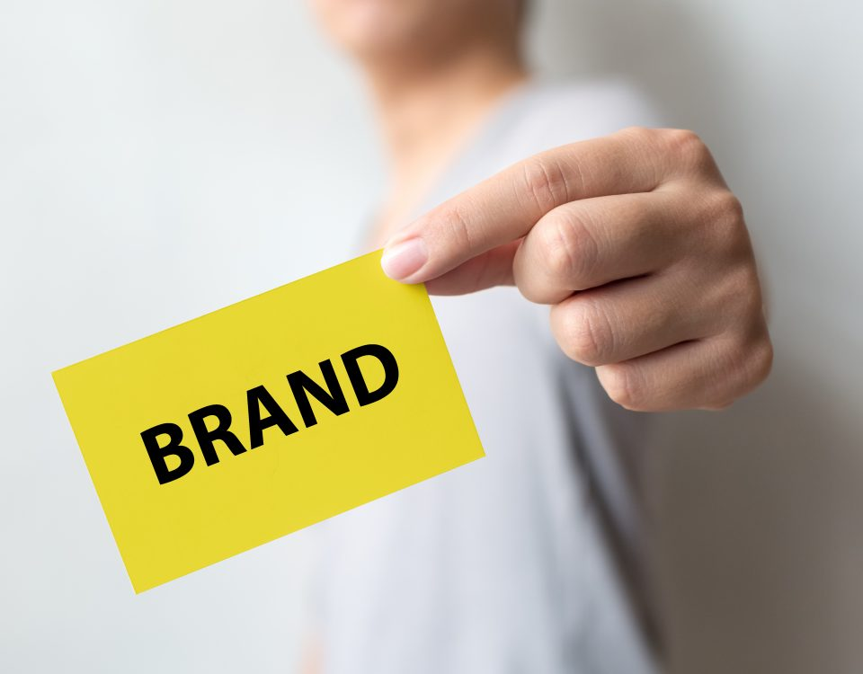 Man holding yellow card and word BRAND. Brand building for success concept